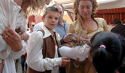 Imagen de la última edición del Mercado Medieval de Tordesillas. Un muchacho ataviado al estilo de la época sostiene una iguana.